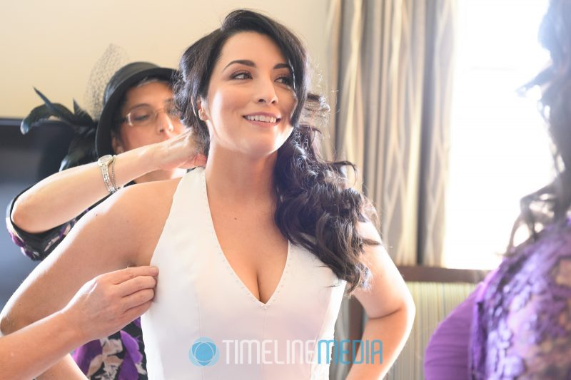 Bride getting ready with her mom and bridesmaids before her wedding ©TimeLine Media