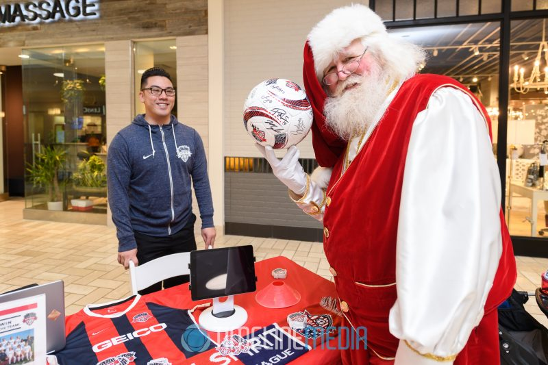 Holding a soccer ball from the Washington Spirit at their booth in Tysons Corner Center 2019 Athleta Holiday Yoga