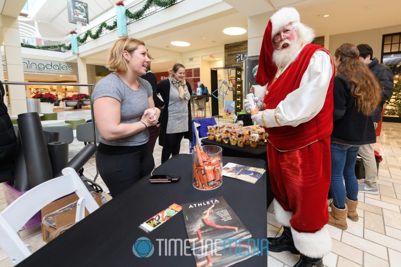 Santa visits the 2019 Athleta booth during their holiday yoga event at Tysons Corner Center