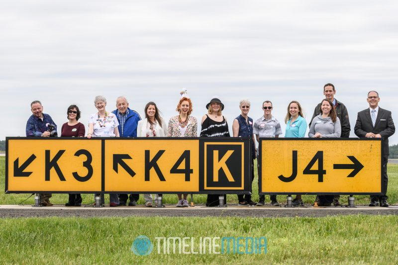 Birthday girl with family and friends at the runway signs at Dulles ©TimeLine Media