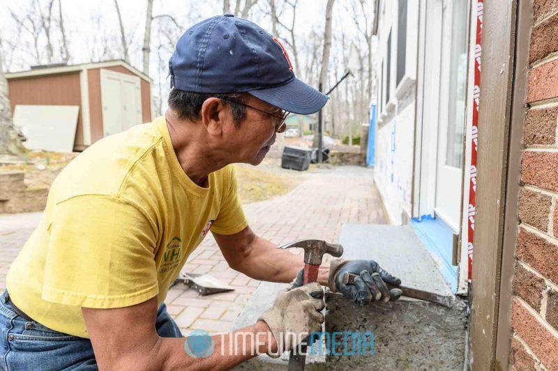 Ricardo finishing a concrete step outside a door ©TimeLine Media